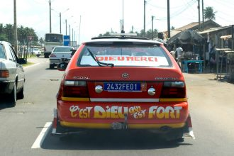 Taxi cabs are painted in orange, and leave space for hand-painted messages, as here they claim 'It's God who is strong' and 'Thanks God' (in French), in Abidjan, Ivory Coast, on November 4, 2010. Photo by Lucas Schifres/Pictobank