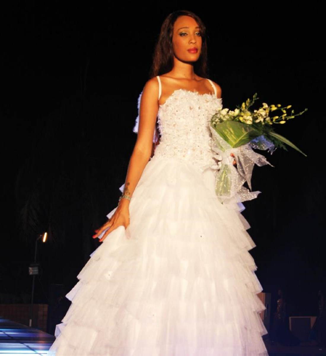Nabila dans une belle robe de mariée, tenant son bouquet de fleurs. Life Mag