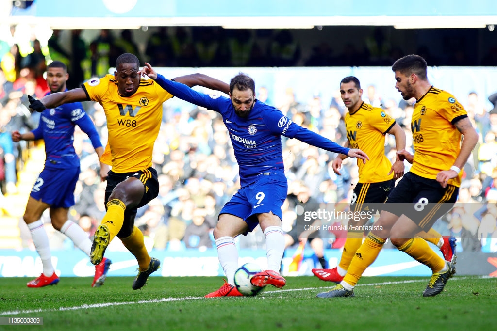 LONDON, ENGLAND - MARCH 10: Gonzalo Higuain of Chelsea (centre) takes a shot as Willy Boly of Wolverhampton Wanderers (L) attempts to block during the Premier League match between Chelsea FC and Wolverhampton Wanderers at Stamford Bridge on March 10, 2019 in London, United Kingdom. (Photo by Chris Brunskill/Fantasista/Getty Images)
